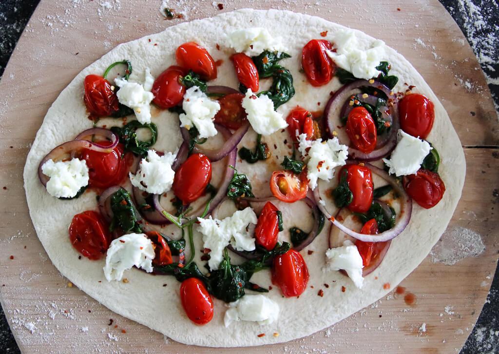 Pizza med tomat, spinat, løk og mozzarella